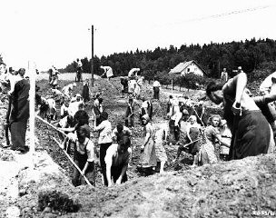 """<p>German civilians from the town of Nammering, under orders of American military authorities, dig graves for victims of a <a href=""""/narrative/2931/en"""">death march</a> from the Buchenwald concentration camp. Germany, May 1945.</p>"""