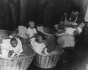 "<p>German propaganda photograph of a kindergarten for German infants promotes the nurturing role of <a href=""/narrative/4164/en"">women</a> on the home front. Germany, 1941.</p>"