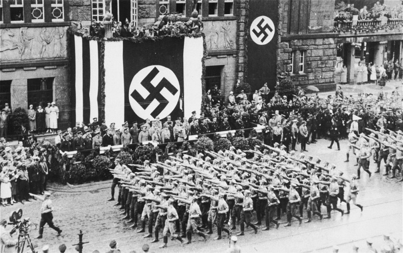 <p>Battalions of Nazi street fighters salute Adolf Hitler during an SA parade through Dortmund. Germany, 1933.</p>
