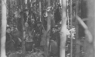 """<p>Jewish partisans, survivors of the <a href=""""/narrative/3636/en"""">Warsaw ghetto uprising</a>, at a family camp in Wyszkow forest. Poland, 1944.</p>"""