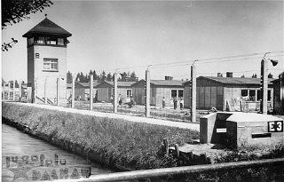 """<p>View of the <a href=""""/narrative/4391/en"""">Dachau</a> concentration camp, after liberation on April 29, 1945. It shows the electrified barbed wire fence, the moat, and a watchtower.</p>"""
