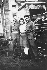 """<p>A <a href=""""/narrative/4750/en"""">Jewish Brigade</a> soldier with two members of """"Kibbutz Buchenwald."""" """"Kibbutz Buchenwald"""" was a group of survivors from the <a href=""""/narrative/3956/en"""">Buchenwald</a> concentration camp who were preparing for agricultural work in Palestine. Antwerp, Belgium, 1946.</p>"""