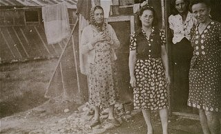 "<p>Women prisoners standing in front of barracks at the <a href=""/narrative/4842/en"">Gurs</a> camp. Gurs, France, ca. 1943.</p>"