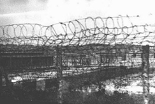 """<p>A section of barbed-wire fencing surrounding the <a href=""""/narrative/4880/en"""">Plaszow</a> camp. Plaszow, Poland, 1943-44.</p>"""