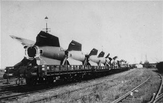 "<p>Sections of V-2 rockets, the so-called Vengeance Weapons, are removed by rail from the <a href=""/narrative/4909/en"">Dora-Mittelbau</a> camp after liberation. Near Nordhausen, Germany, June 1945.</p>"