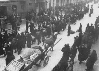 "<p>Jews deported from Germany and Austria march towards the <a href=""/narrative/2152/en"">Lodz</a> ghetto. Lodz, Poland, October 1941.</p>"