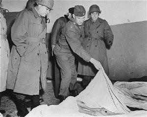 """<p>Members of a US congressional committee investigating German atrocities view the emaciated body of a dead prisoner at the <a href=""""/narrative/4909/en"""">Dora-Mittelbau</a> concentration camp, near Nordhausen. Germany, May 1, 1945.</p>"""
