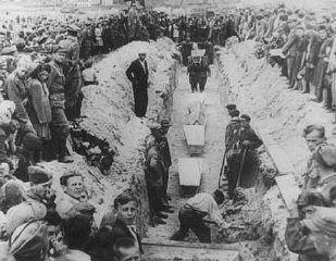 "<p>Mourners crowd around a narrow trench as coffins of pogrom victims are placed in a common grave, following a mass burial service. <a href=""/narrative/11504/en"">Kielce</a>, Poland, after July 4, 1946.</p>"