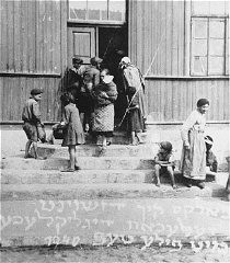 "<p>Women and children gather at the door of a soup kitchen maintained by the <a href=""/narrative/5002/en"">American Jewish Joint Distribution Committee</a>. The text in Yiddish reads ""The fortunate ones with full bowls."" Zelechow, Poland, 1940.</p>"