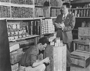 "<p>Morris Laub (right), <a href=""/narrative/5002/en"">American Jewish Joint Distribution Committee</a> director for <a href=""/narrative/26091/en"">Cyprus</a>, reviews supplies sent for the 12,000 Jews still interned on the island. Cyprus, December 9, 1948.</p>"