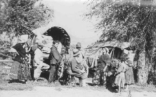 <p>Photographer J. Kolarcik sits with a group of nomadic Roma (Gypsies). This photograph was probably taken in Czechoslovakia, 1939.</p>