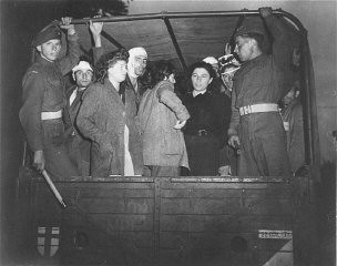 "<p>British soldiers guard Jewish refugees, forcibly removed from the refugee ship <a href=""/narrative/5265/en""><em>Exodus 1947</em></a>, on trucks leaving for Poppendorf <a href=""/narrative/6365/en"">displaced persons</a> camp. Photograph taken by Henry Ries. Kuecknitz, Germany, September 8, 1947.</p>"