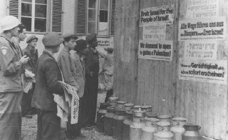 <p>Jewish survivors in a displaced persons camp post signs calling for Great Britain to open the gates of Palestine to the Jews. Germany, after May 1945.</p>