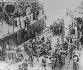 "<p>British soldiers supervise the transfer of refugees from the <a href=""/narrative/5265/en"">Exodus 1947</a> to deportation ships which will take them to France. Haifa, Palestine, July 20, 1947.</p>"