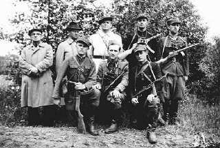 """<p class=""""document-desc moreless"""">General Michael (Rola) Zymierski (top row, center), commander of the Polish communist Armia Ludowa, poses with a partisan unit in the Parczew Forest. The partisan unit includes the Jewish physician, Michael Temchin (bottom right).</p>"""