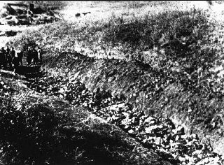 "<p>Soviet investigators (at left) view an opened mass grave at <a href=""/narrative/5337/en"">Babi Yar</a>. Kiev, Soviet Union, 1944</p>"