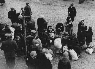 "<p>Jewish families with bundles of belongings during deportation from the <a href=""/narrative/3182/en"">Kovno</a> ghetto in <a href=""/narrative/5762/en"">Lithuania</a> to <a href=""/narrative/6400/en"">Riga</a> in neighboring <a href=""/narrative/5729/en"">Latvia</a>. Kovno, Lithuania, 1942.</p>"