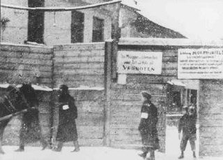 "<p>This photograph shows the Rudnicki Street entrance to the <a href=""/narrative/3169/en"">Vilna</a> ghetto. The signs on the fence claim there is danger of contagion and prohibit the bringing of food or wood into the ghetto. Photograph taken in 1941–42.</p>"