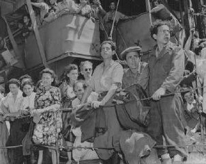 "<p>Refugees crowd the rail of the Aliyah Bet (""illegal"" immigration) ship <em>Josiah Wedgewood</em>, anchored at the Haifa port. British soldiers transported the passengers to the Athlit internment center. Palestine, June 27, 1946.</p>"