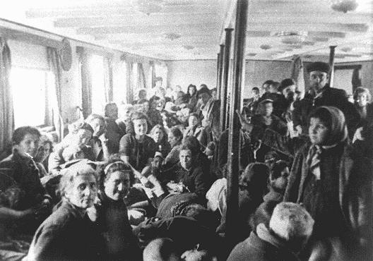 """<p>Thracian Jews crowded into an interior room of the <em>Karađorđe, </em>used asa deportation ship, just before it left the Danube River port of Lom. From Lom they were loaded onto four Bulgarian ships and taken to Vienna, where they were put on trains bound for the Treblinka killing center in occupied Poland. Lom, <a href=""""/narrative/5955/en"""">Bulgaria</a>, March 1943.</p>"""