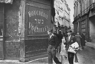 "<p>A young man in the Jewish quarter of Paris wears the mandatory <a href=""/narrative/11750/en"">Jewish badge</a>. Paris, France, after June 1942.</p>"