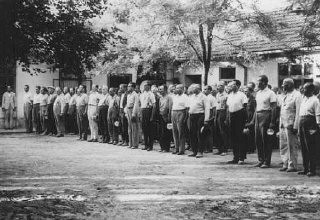 "<p>With bowls in hand, conscripts of a Jewish Hungarian labor unit wait for food. Abony, <a href=""/narrative/6206/en"">Hungary</a>, 1940.</p>"