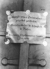 "<p>A notice reads ""Business closed by the police due to profiteering. Owner in protective custody at Dachau."" Signed by police chief <a href=""/narrative/10813/en"">Heinrich Himmler</a>. Munich, Germany, April or May 1933.</p>"