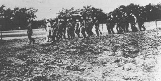 """<p>German soldiers lead blindfolded <a href=""""/narrative/6590/en"""">Polish hostages</a> to an execution site. Olkusz, Poland, July 16, 1940.</p>"""