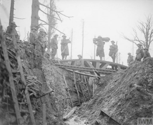 <p>British troops at the site of a former German trench following the withdrawal of German troops to the Hindenburg line on the western front in World War I. This photograph shows a trench bridge over a German trench. Gommecourt, France, 1917.</p>