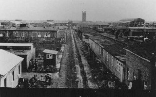 """<p>View of the Neuengamme concentration camp.Prisoners stand behind the fence that separates the """"protective custody"""" camp from the manufacturing sectors of the camp. In the distance are the crematorium and the Walther armaments works. Photograph taken between 1940 and 1945, Neuengamme, Germany.</p> <div class=""""datapair""""></div>"""