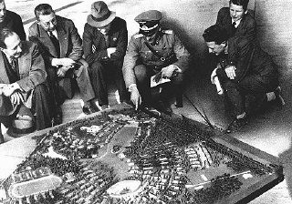 """<p>The Nazis spent large sums in preparation for the <a href=""""/narrative/7139/en"""">Olympic games</a>. Here, German officials show the extent of the Olympic village using a scale model. <a href=""""/narrative/5908/en"""">Berlin</a>, Germany, July 1936.</p>"""