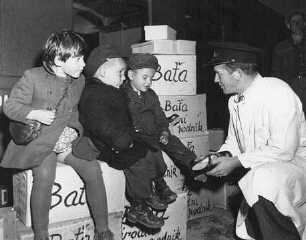 "<p>Jewish orphans after the Holocaust are fitted with shoes from the <a href=""/narrative/7232/en"">United Nations Relief and Rehabilitation Administration</a> (UNRRA), en route to Allied occupation zones in Germany and Austria. Prague, Czechoslovakia, August 25, 1946.</p>"