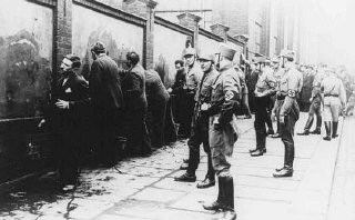 <p>Political opponents of the Nazis, guarded by SA (Storm Troopers), are forced to scrub anti-Hitler slogans off a wall shortly after the Nazi assumption of power. Germany, March 1933.</p>