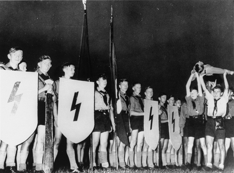 """<p>A Hitler Youth ceremony, typical of those conceived by Baldur von Schirach. They aimed to strengthen dedication to Hitler. Members recited verses, sang patriotic songs, and performed """"mock funerals"""" for """"fallen comrades."""" Germany, date uncertain.</p>"""