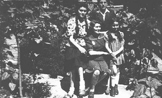 """<p>The Aigner family of Nove Zamky, Czechoslovakia. The town was occupied by Hungary. Laszlo (Leslie) Aigner (standing, back) survived the <a href=""""/narrative/3673/en"""">Auschwitz</a> camp; his mother (seated) and sister Marika (standing, right) were gassed there. May 1944.</p>"""