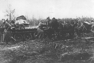 <p>A German army column struggles through the mud, past a destroyed Soviet tank. Nevel, Soviet Union, fall 1943.</p>