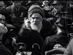 <p>Huge crowds of well wishers gather in the streets on the occasion of the wedding of the Munkács rabbi's 18-year-old daughter, Frime Chaye Rivke. The Grand Rabbi of Munkács (Mukacevo), Chaim Elazar Shapiro, father of the bride, makes a speech in Yiddish exhorting Jews in America to continue to keep Shabbes (to observe the sabbath day). The wedding party then enters the synagogue grounds, and the cantor sings blessings beneath the wedding canopy. The wedding concludes with festive klezmer music. The marriage had been arranged six years earlier, though the bride and groom did not meet until their wedding day. Newspaper accounts indicate that some 20,000 people attended the celebrations.</p>