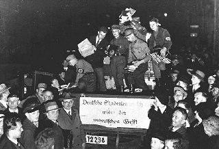 """<p>Students and members of the SA unload books deemed """"un-German"""" during the book burning in Berlin. The banner reads: """"German students march against the un-German spirit."""" Berlin, Germany, May 10, 1933.</p>"""