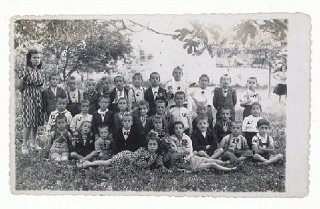"<p>Gavra Mandil and his family narrowly escaped death in German-held <a href=""/narrative/6153/en"">Yugoslavia</a> by fleeing to Italian-occupied Albania. There Gavra attended a school in Kavaja that had both Muslim and Christian pupils. He is seated on the far right in the first row. June 1943.</p>"
