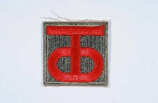 "<p>Insignia of the <a href=""/narrative/7839/en"">90th Infantry Division</a>. Called the ""Tough Ombres,"" the 90th Infantry Division was raised from draftees from the states of Texas and Oklahoma during <a href=""/narrative/28/en"">World War I</a>. The divisional insignia incorporates the letters ""T"" and ""O"" to symbolize both states. These letters later yielded the nickname ""Tough Ombres,"" symbolizing the esprit de corps of the unit. The 90th was also sometimes called the ""Alamo"" division during <a href=""/narrative/2388/en"">World War II</a>.</p>"