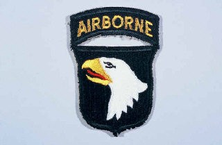 "<p>Insignia of the <a href=""/narrative/7949/en"">101st Airborne Division</a>. The nickname of the 101st Airborne Division, ""Screaming Eagles,"" originates from the division's insignia, a bald eagle on a black shield. ""Old Abe"" was the eagle mascot of a Wisconsin regiment during the Civil War. The 101st was formed as a reserve unit in Wisconsin shortly after World War I and included ""Old Abe"" as part of the division's insignia.</p>"