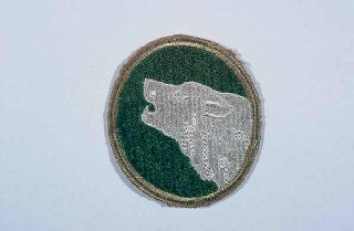 "<p>Insignia of the <a href=""/narrative/7957/en"">104th Infantry Division</a>. The nickname of the 104th Infantry Division, ""Timberwolf,"" originated from the division's insignia, a gray timberwolf. The timberwolf, native to the Pacific Northwest, was chosen as representative of the area where the division was formed in 1942.</p>"