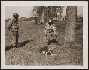 "<p>An American medic and soldier stand by the corpse of a prisoner shot on the road near <a href=""/narrative/8101/en"">Gardelegen</a>. The prisoner was shot by the SS when he was too exhausted to continue on a death march. Germany, April 14-18, 1945.</p>"