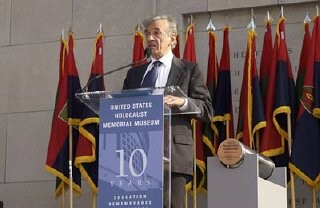 "<p>Elie Wiesel became Founding Chairman of the United States Holocaust Memorial Council in 1980. Here, he speaks at a ceremony held during the Tribute to Holocaust Survivors, one of the Museum's tenth anniversary events. Flags of <a href=""/narrative/8007/en"">US Army liberating divisions</a> form the backdrop to the ceremony. Washington, DC, November 2003.</p>"