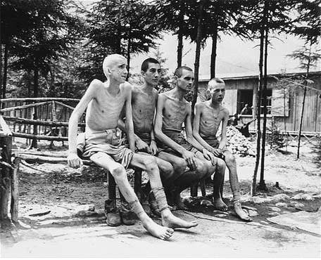 """<p>Four emaciated survivors sit outside in the newly liberated Ebensee concentration camp. Photograph taken by Signal Corps photographer <a href=""""/narrative/8148/en"""">J Malan Heslop</a>. Ebensee, Austria, May 8, 1945.</p>"""