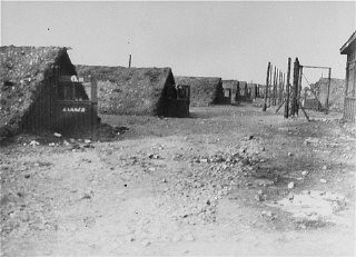 """<p>A view of barracks in the Kaufering network of subsidiary camps of the <a href=""""/narrative/4391/en"""">Dachau</a> concentration camp. Landsberg-Kaufering, Germany, after April 27, 1945.</p>"""