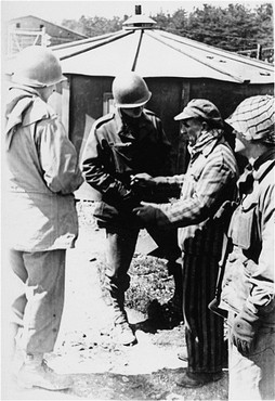 """<p>A survivor of Kaufering IV, one of the <a href=""""/narrative/4391/en"""">Dachau</a> subcamps in the Landsberg-Kaufering area, withUS soldiers after liberation. Kaufering, Germany, after April 27, 1945.</p>"""