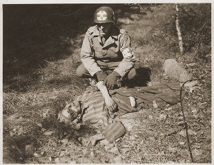 <p>An American soldier kneels by the corpse of a prisoner on the roadside near Gardelegen. The prisoner was shot by the SS when he was too exhausted to continue on a death march. Germany, April 14-18, 1945.</p>