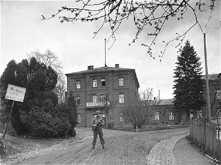 <p>An American soldier stands guard in front of the Hadamar Institute. The photograph was taken by an American military photographer soon after the liberation. Germany, April 5, 1945.</p>