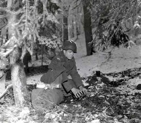 "<p>A soldier prepares to bed down for the night in a Belgian forest during the <a href=""/narrative/8156/en"">Battle of the Bulge</a>. December 21, 1944. <a href=""/narrative/8129/en"">US Army Signal Corps</a> photograph taken by J Malan Heslop.</p>"